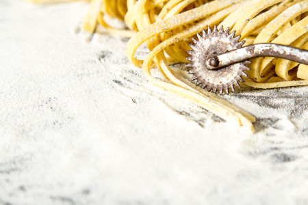 Homemade italian tagliatelle with flour. Dark background