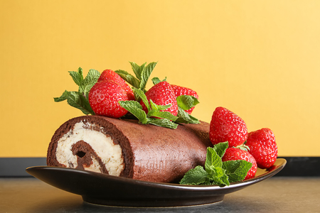 Delicious homemade chocolate cake with strawberries and mint. Dark background. Celebratory dinner