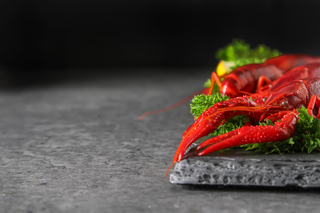 Delicious boiled crayfish close-up with lemon and parsley. Dark background. Dinner with seafood