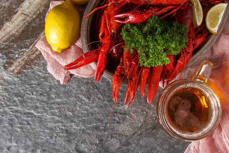 Delicious boiled crayfish close-up, lemon and parsley with beer. Dark background. Dinner with seafood Stock Photo