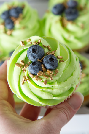 Birthday cupcake with green cream. White background