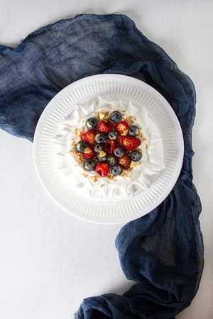 Pavlovs dessert with delicate cream and fresh berries of raspberries and blueberries. Light background Stock Photo