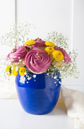 A cupcake for a holiday with flowers. Light background