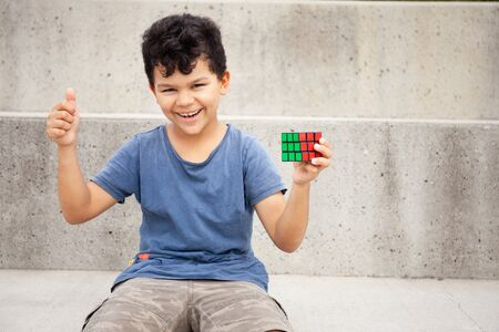 a portrait of a happy boy 9 years old, holding a solved puzzle cube and smiling