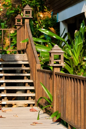 Wooden designed handrail of a pathway outsied of a garden. photo