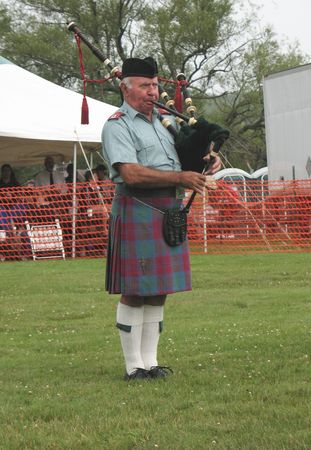 lindsay: A piper playing with his band in a circle, competing against other pipe bands for honours. This piper is wearing the Ancient Lindsay tartan.