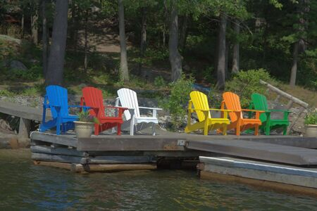 Six Chairs of different colours are resting on the deck and taking in the sunshine Фото со стока