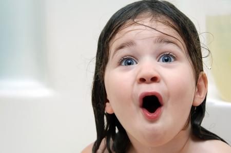 Meisje reageert op Bathtime Haar mond is open van verbazing en haar haar is drijfnat Stockfoto