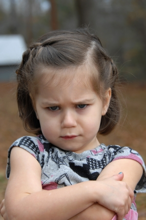 rebelling: Arms crossed and eyebrows puckered, this little girl is upset and pouting   She is standing outside  Stock Photo