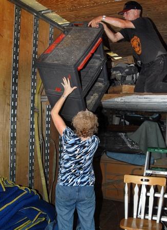 Couple work together to unload their moving van   Husband is handing tool box to wife standing on floor   It is hot work inside van