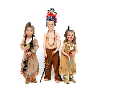 Three little indians, dressed in costumes and holding weapons, greet Thanksgiving with solemn faces.  They stand in all white room with space for personalization. Banque d'images