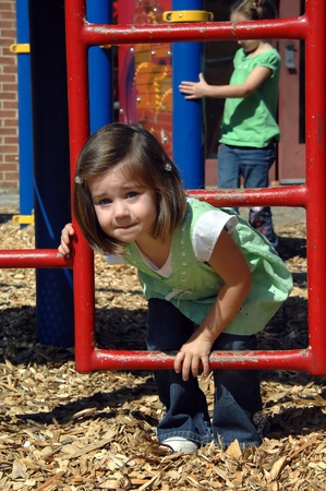 playground equipment: Preschool morning break includes exercise time on the playground equipment.  Little girl climbs through metal ladder.  Wood chips cover ground for safety.