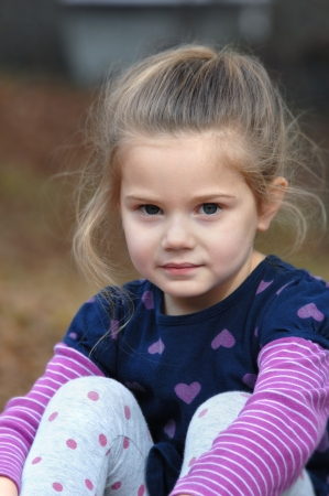contemplative: Adorable little girl sits serene and still.  Her face expresses a thoughtful and contemplative look as she enjoys the outdoors.