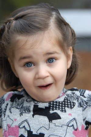 Little girl is amazed and surprised and shows it with jaw dropped, mouth open and eyebrows raised.  She is wearing a pink and grey dress. Stock Photo - 14566218
