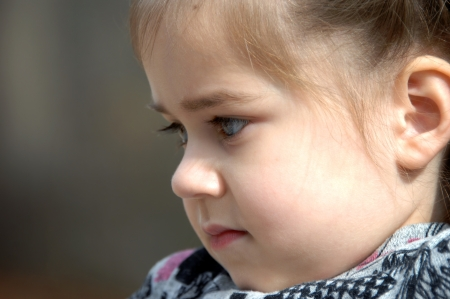 lost in thought: Lost in thought, this little girl is in profile and close up.  She is resting her chin on her chest. Stock Photo