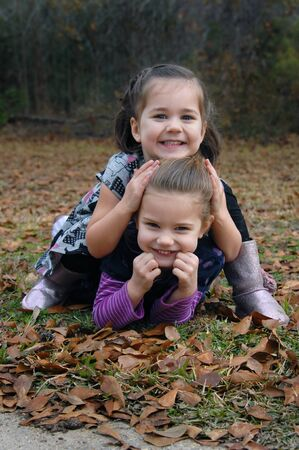 Two sisters tumble in the grass and leaves on a Fall morning.  One sister sits on the other one and they both are smiling and giggling together. photo