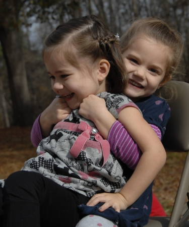 Two little girls laugh and giggle as one sits on the lap of the other   They are both sitting outdoors in a metal folding chair  photo