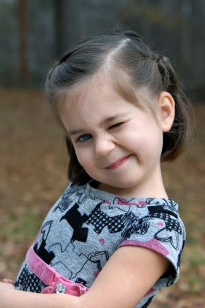 Cute little girl tilts her head and winks   She is outdoors and is wearing a grey and pink print dress  photo