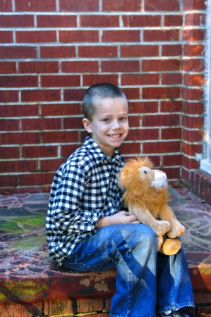 unkept: Little boy sits on the steps of his apartment home   Home is unkept with cracked bricks and peeling paint   He is holding his stuffed animal and smiling happily