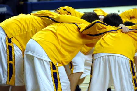 High school varsity basketball team huddles together before game start.  Uniforms are yellow, purple and white.