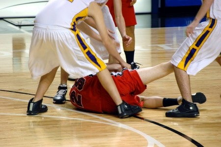 Boys player on basketball team hangs on for dear life. He is on the floor and surrounded by the opposition.