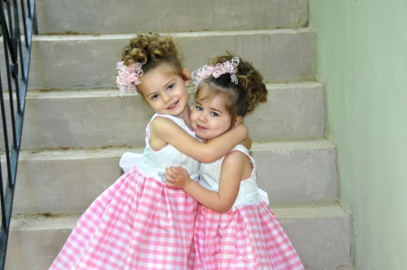curly hair child: Two sisters dressed identically embrace on Easter Sunday morning   They are both smiling and happy