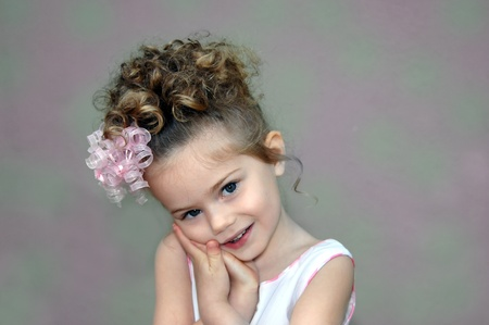 Little girl leans her head in her hands   She has curls all over her head and a sweet curly ribbon bow decorating it   Background is mottled green and pink Stock Photo - 14583801