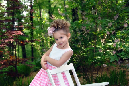 Beautiful little girl is wearing a pink and white gingham Easter dress   She is leaning on a white rocking chair and smiling   Nature Stock Photo - 14583804