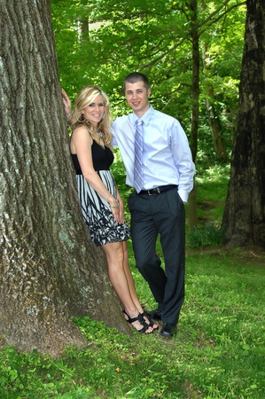 Husband and wife stand in the Tennessee woods and enjoy a sunny afternoon under the trees   She is wearing a dress and he is wearing dress slacks and shirt and tie   Both are smiling happily