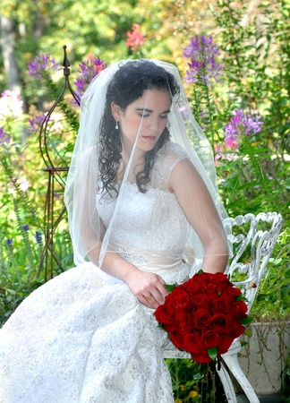 Beautiful young bride is sitting in a garden surrounded by flowers.  She is dreamily gazing at her red rose bouquet.  Veil is covering her face. photo