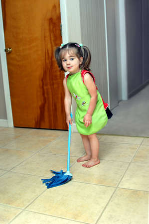 Little girl learns the lesson of hard work.  She is holding a blue, play mop and wearing a bright green apron.  She has a weary look on her face. Stock Photo - 14618296