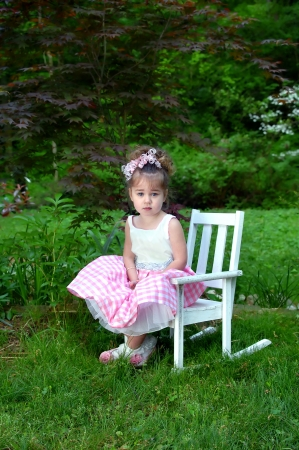 Beautiful little girl poses on Easter Sunday morning   She is wearing a pink and white gingham dress with net slip   Her hair is in ringlets and has a pink curly ribbon bow Stock Photo - 14618337