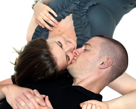 Couple lay close together on an all white floor   Angle is high and catches soft kiss on the cheek   Female is wearing grey and male is wearing black  photo