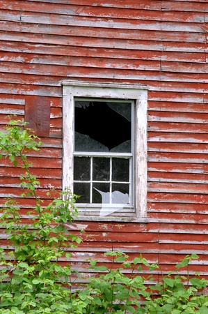 Rustic, red, wooden barn has broken glass window panel Stock Photo - 14627677