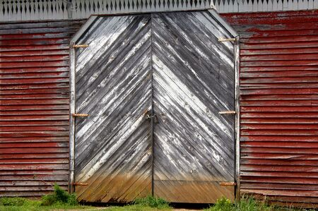 diagonal lines: Rustic, red, wooden barn has boards running diagonally metting at center of double doors.  Red and white paint is peeling. Stock Photo