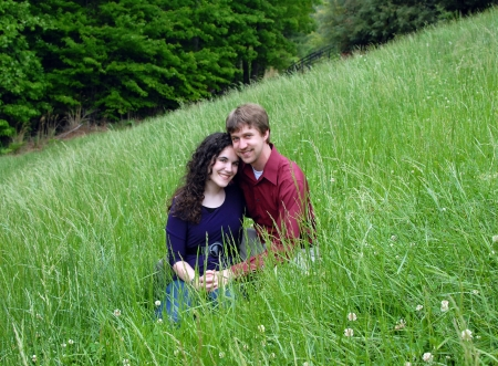 Couple enjoy spingtime in the tall green grass of an Appalachian Mountain meadow   They are sitting close together smiling  photo