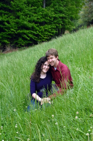 Couple sit cheek to cheek in an Appalachian mountain meadow in North Carolina   His arm is around her and they are both smiling as they kneel in tall green grass  photo