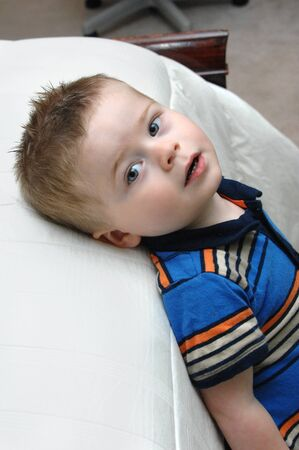 High angle shot of little boy as he leans back against his bed