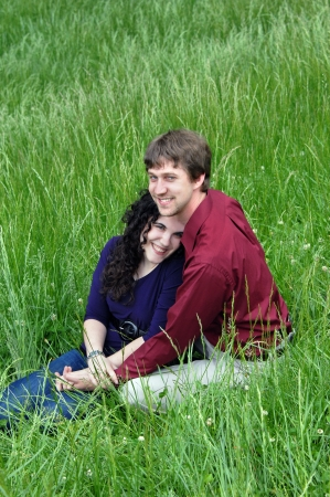 Happiness glows from young couples faces as they kneel in a meadow and are surrounded by tall gree, spring grass  photo