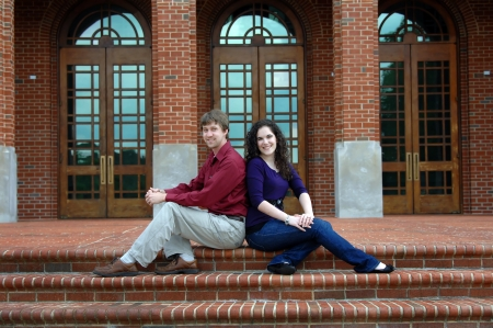 college dorm: Couple sit back to back on the front steps of a college dorm   They are both smiling and happy  Stock Photo