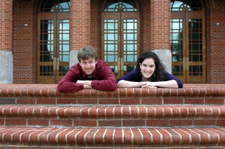 Young attractive couple lay on the brick steps of the entry to a college building   They are relaxed and happy and both are smiling  photo
