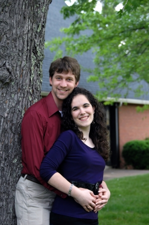 Couple lean against a tree   Both are smiling happily and are loving   Brick building in the background  photo