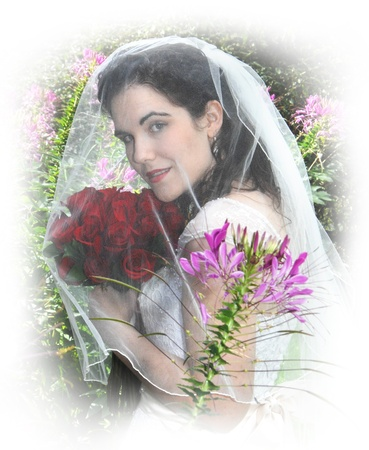 Soft white surrounds dreaming, young bride as she looks up from beneath her veil  Her wedding day has passed in a blur and she dreamily looks back over the ceremony   She is holding a red rose bouquet and stand in a garden filled with flowers  photo
