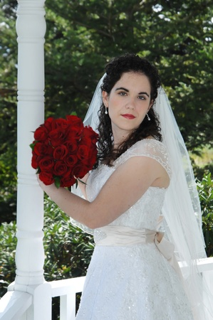 Beautiful bride poses on white wooden balcony   She holds her bouquet of red roses besides her face  photo