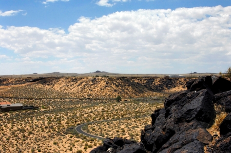 Petroglyph National Monument view includes distant cinder cones of dormant volcanoes just outside of Albuquerque.  Basalt rocks in forground containt hundreds of preserved petroglyphs. photo