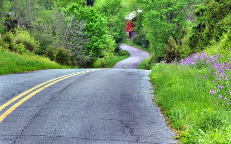 Curving road hugs Appalachian mountain as it curves and winds the country byways of Tennessee   Red wooden barn can be seen at bottom of hill and wildflowers and spring grass color countryside  photo