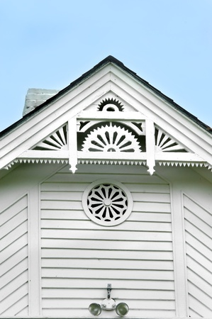 Beautiful whimsical eaves show wood craftsmanship   White frame house has been well maintained and with fan shaped woodworking on older home still intact  photo