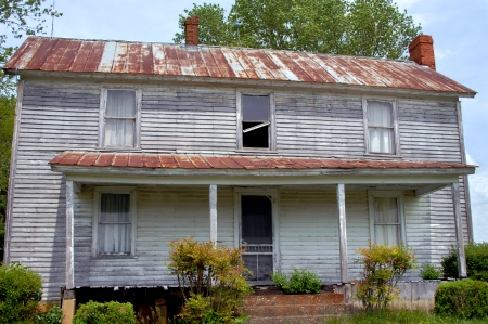 Vintage farm house has tin roof, clapboard sides, chimneys and front porch  Standard-Bild