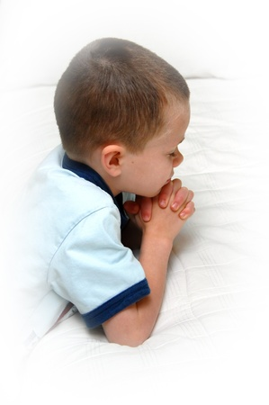 Small child kneels besides his bed and folds his hands in prayer.  He is wearing a blue shirt and kneeling besides a white covered bed. Archivio Fotografico