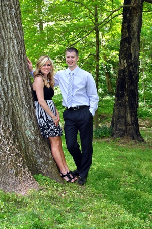 Couple enjoy each others company.  They are posing besides a large tree in the Tennessee forest near Kingsport.  Both are smiling naturally. photo